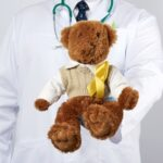 pediatrician-white-coat-blue-latex-gloves-holds-brown-teddy-bear-with-yellow-ribbon-sweater-concept-discuss-about-autism-spectrum-disorders-with-vios-viosapp-telemedicine