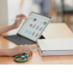 Nurse practitioner using EHR telehealth platform to schedule virtual patient care with a laptop
