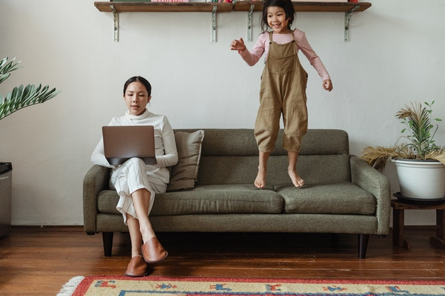 young mother doing telemedicine appointments with viosapp vios app platfrom with her child jumping on the sofa