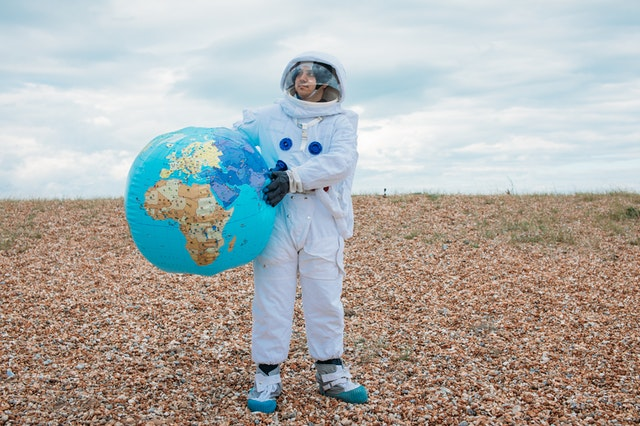 earth astronoat holding plaent balloon