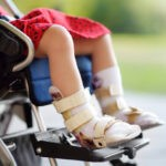 child with cerebral palsy in wheelchair with leg braces waiting for pediatrician telemedicine review on viosapp vios clinic