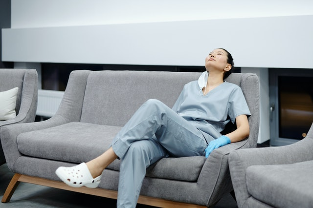 exhausted doctor surgeon in the physician lounge waiting for the next procedure