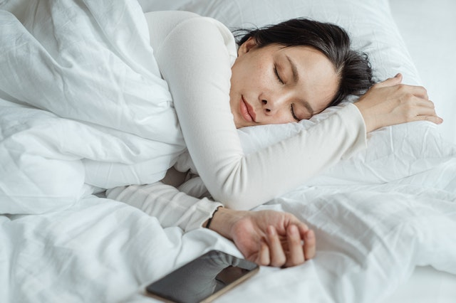 woman sleeping in bed with white duvet next to her iphone 10