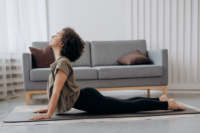 woman with afro practising yoga at home